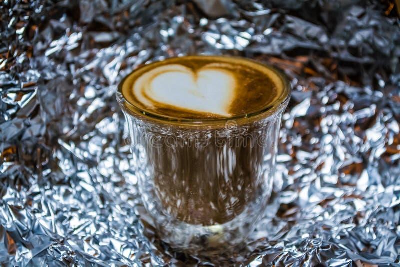 Capuchino con arte del latte en vidrio transparente con las paredes dobles en el fondo de una hoja Coraz?n Bebida fuerte con cafe fotografía de archivo libre de regalías