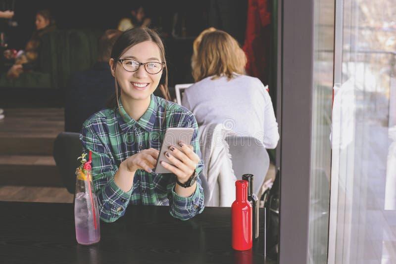 Capuchino de consumición feliz de la mujer joven, latte, macchiato, té, usando la tableta y hablar en el teléfono en una cafeterí fotografía de archivo libre de regalías