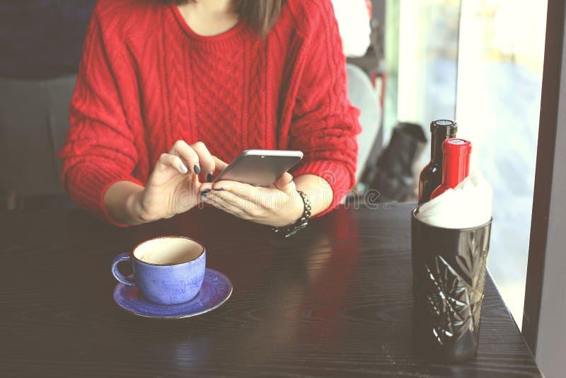 Capuchino de consumición feliz de la mujer joven, latte, macchiato, té, usando la tableta y hablar en el teléfono en una cafeterí foto de archivo