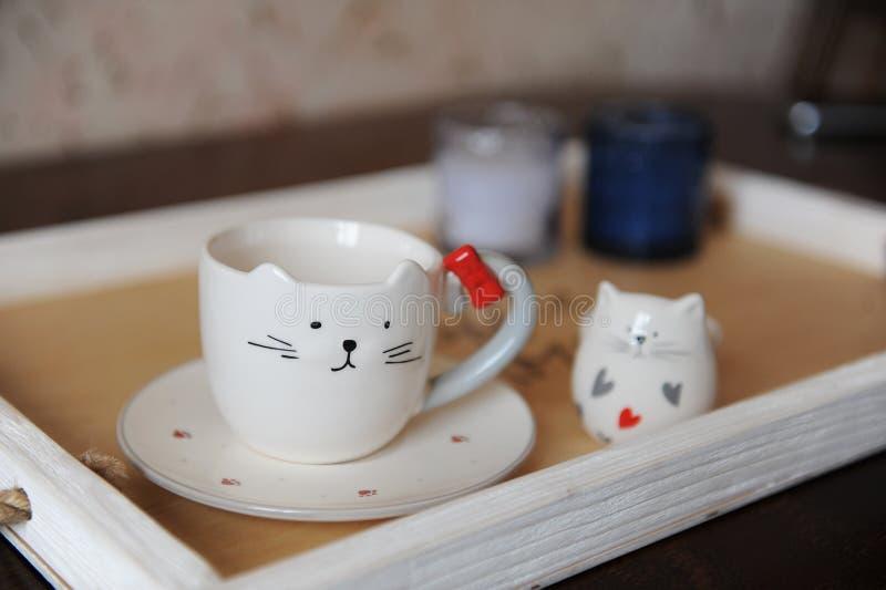 Capuchino del café en taza linda en la forma del gato En una bandeja de madera Velas en el fondo foto de archivo libre de regalías