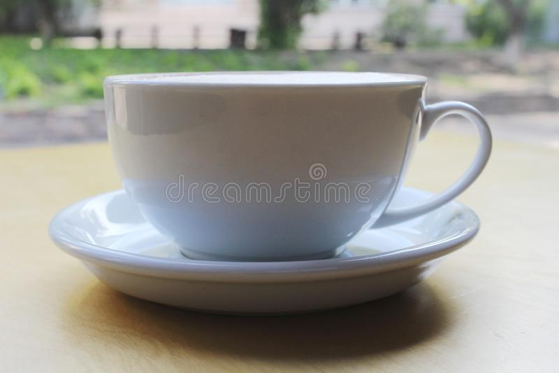 Capuchino o latte con la espuma espumosa, primer azul de la opini?n superior de la taza de caf? aislado en el fondo blanco Café y imágenes de archivo libres de regalías