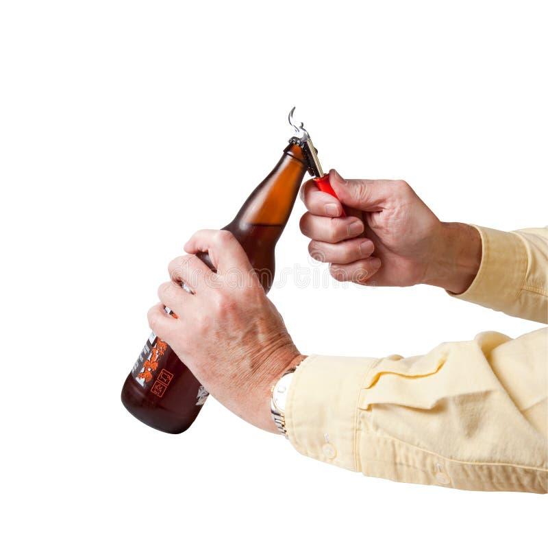 Capuchon étant retiré de la bouteille à bière photographie stock