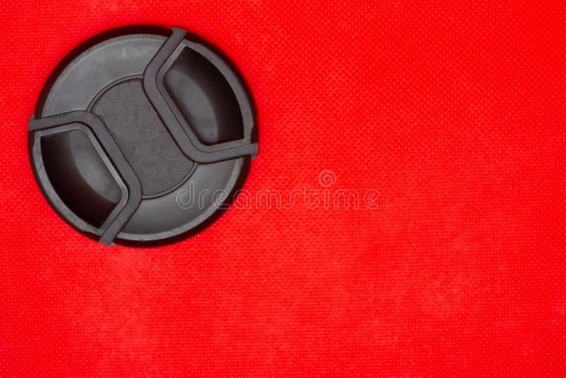 Capuchon d'objectif noir de cercle pour l'objectif de caméra de DSLR sur un fond rouge riche photo libre de droits
