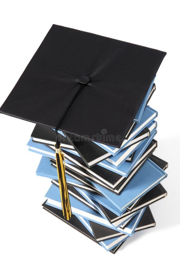 Capuchon et livres de graduation photos stock
