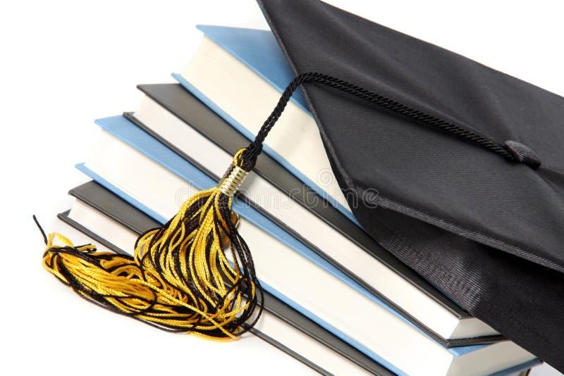 Capuchon et livres de graduation photo stock