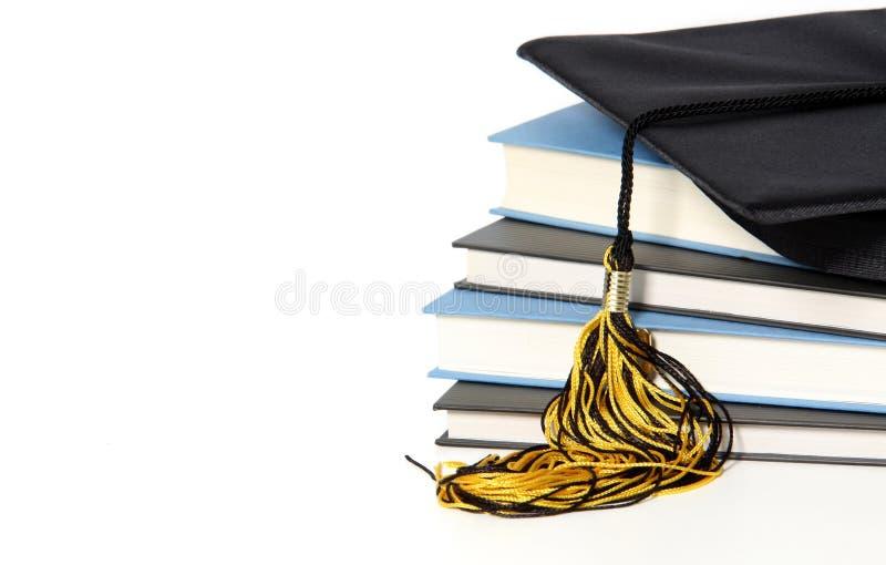 Capuchon et livres de graduation images stock