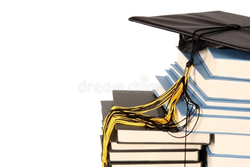 Capuchon et livres de graduation photographie stock libre de droits