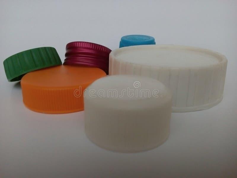 Capuchons de bouteilles en plastique de différentes formes et couleurs sur fond blanc image stock