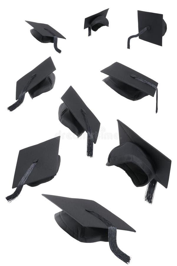 Capuchons de graduation sur le blanc images stock