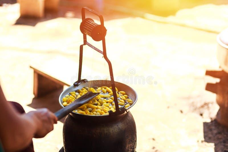 Capullos amarillos de ebullición del gusano de seda por la caldera para hacer el hilo de seda fotos de archivo libres de regalías