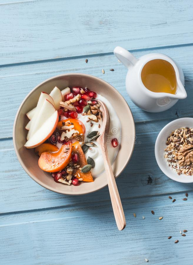 Caqui, manzana, nueces, granadas, semillas y yogur natural Concepto sano de la comida en el fondo azul, visión superior Fruta y G fotos de archivo