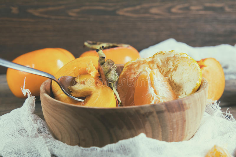 Caquis e frutos frescos das tangerinas na bacia imagem de stock royalty free