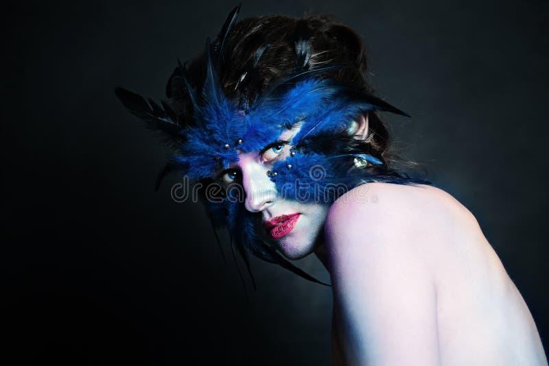 Carácter creativo de Art Halloween Mujer modelo perfecta con las plumas negras y azules, maquillaje del pájaro imagen de archivo