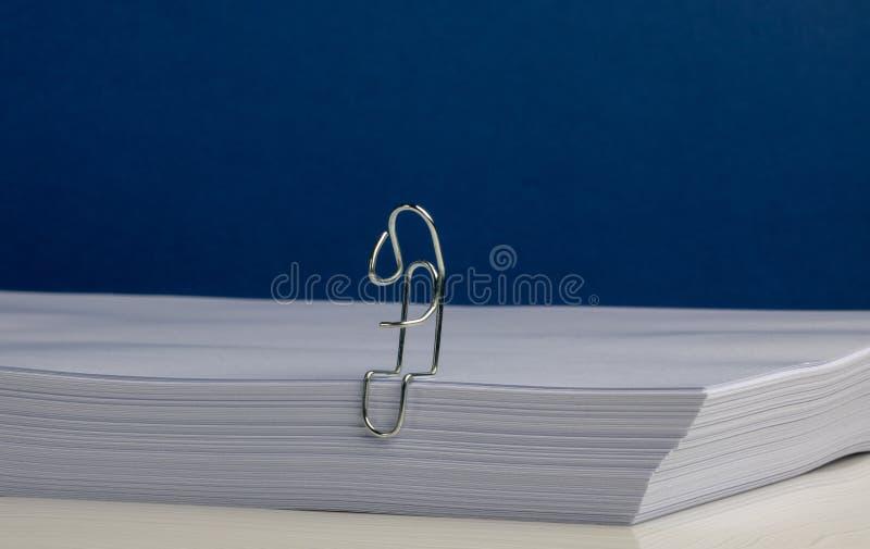 Carácter del clip de papel en pensamiento o reflexión en la resma de papel imagen de archivo libre de regalías