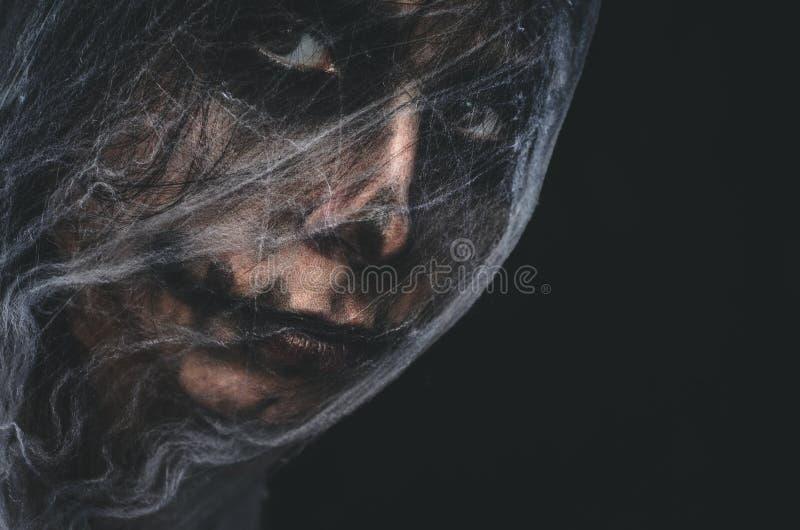 Carácter espeluznante cubierto con el spiderweb en fondo negro imagen de archivo