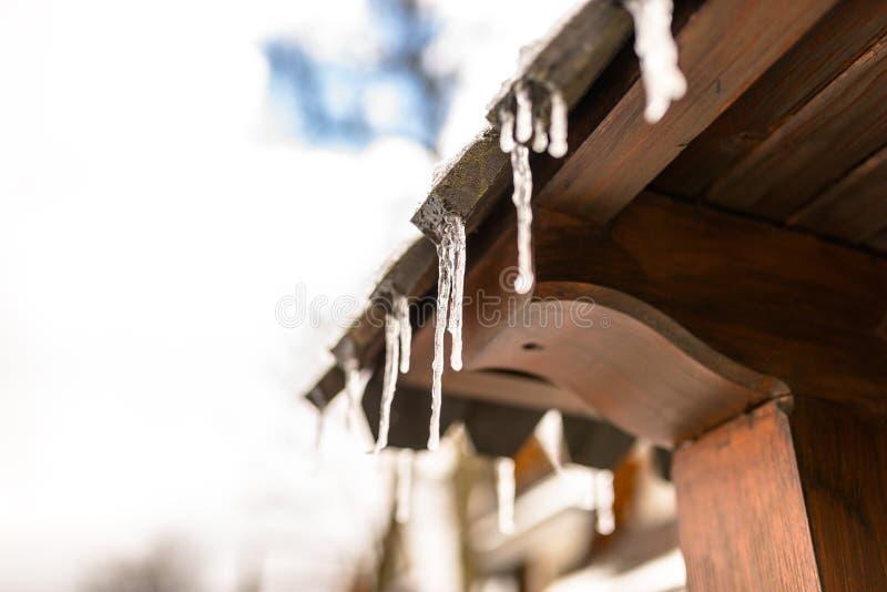 Carámbanos colgantes del tejado de un edificio de madera en un día escarchado del invierno, mucha nieve en el tejado imagen de archivo