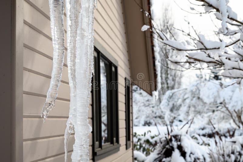 Carámbanos contra una casa marrón clara y un paisaje nevoso blanco fotos de archivo libres de regalías