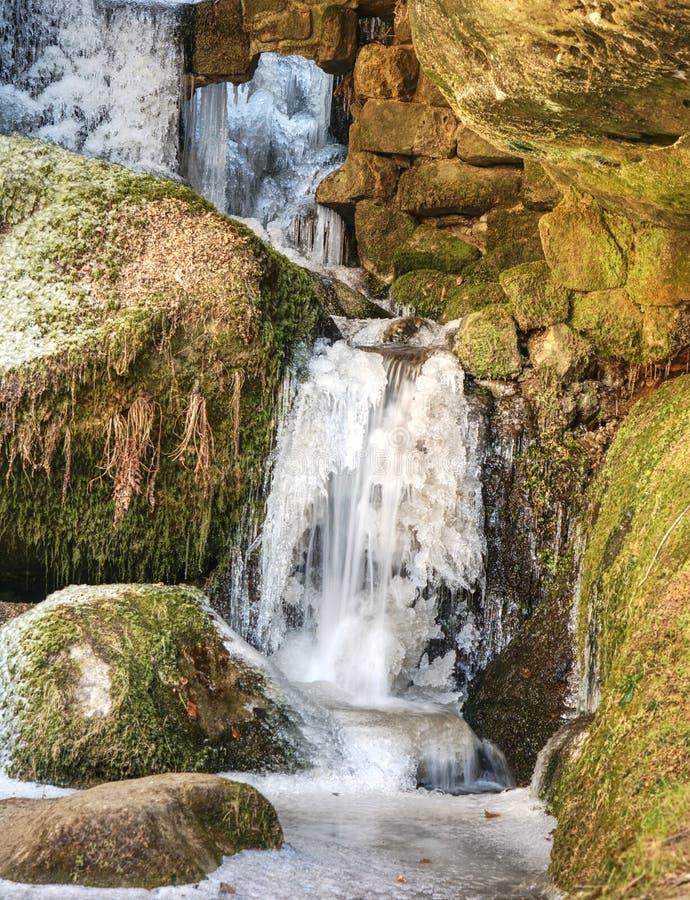 Carámbanos en cascada congelada Nevado y piedras y cantos rodados helados con descensos imagen de archivo libre de regalías