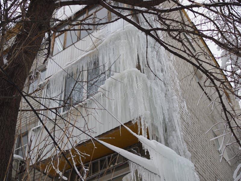 Carámbanos enormes que cuelgan en los balcones de la casa y de los alambres fotografía de archivo