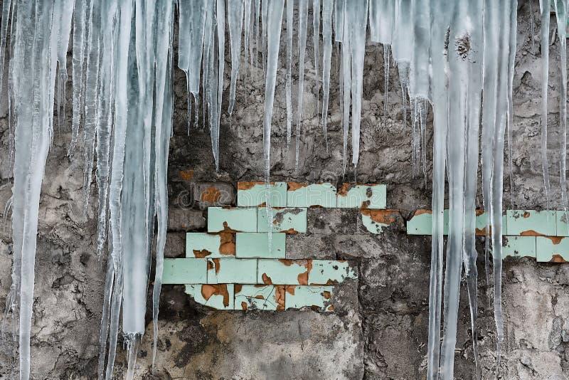 Carámbanos que cuelgan del tejado del edificio de ladrillo viejo con los cubos de las tejas viejas, hielo acre traumático, deshie foto de archivo libre de regalías