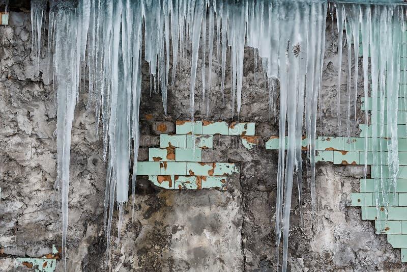 Carámbanos que cuelgan del tejado del edificio de ladrillo viejo con los cubos de las tejas viejas, hielo acre traumático, deshie fotografía de archivo