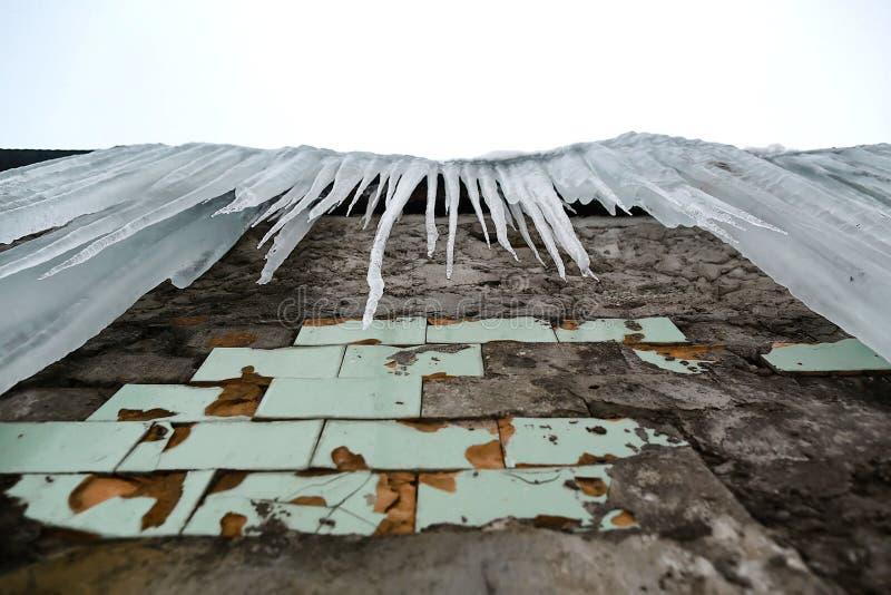 Carámbanos que cuelgan del tejado del edificio de ladrillo viejo con los cubos de las tejas viejas, hielo acre traumático, deshie imagen de archivo libre de regalías