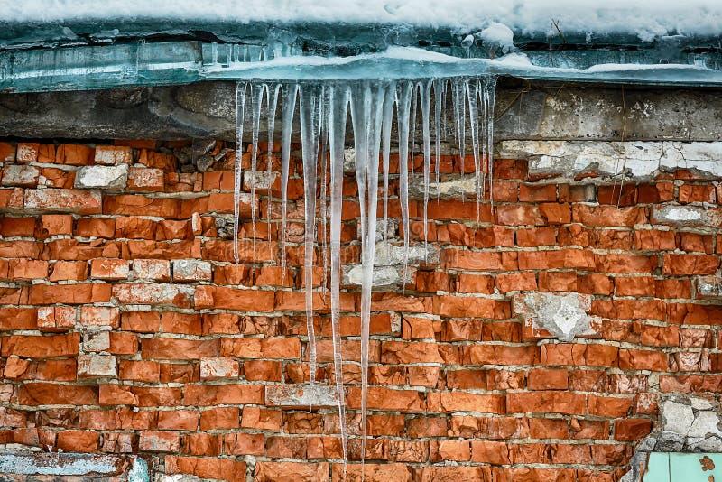 Carámbanos que cuelgan del tejado del edificio de ladrillo viejo, hielo acre traumático, deshielo en la primavera temprana imagen de archivo