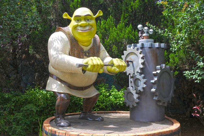 Caráter de Shrek que gerencie uma catraca da bomba de água da mão velha fotografia de stock