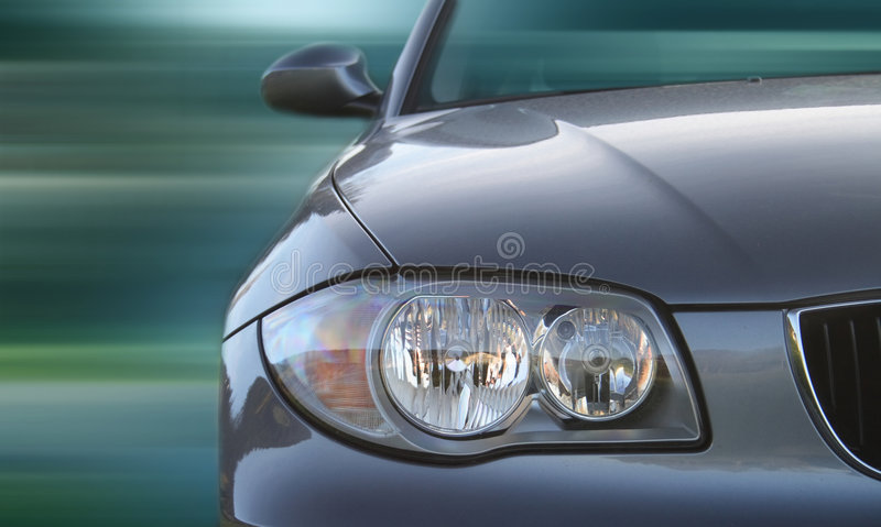 Car. Front of a car with a blurred background. Metallic paint texture on car, not noise. Focus on lights