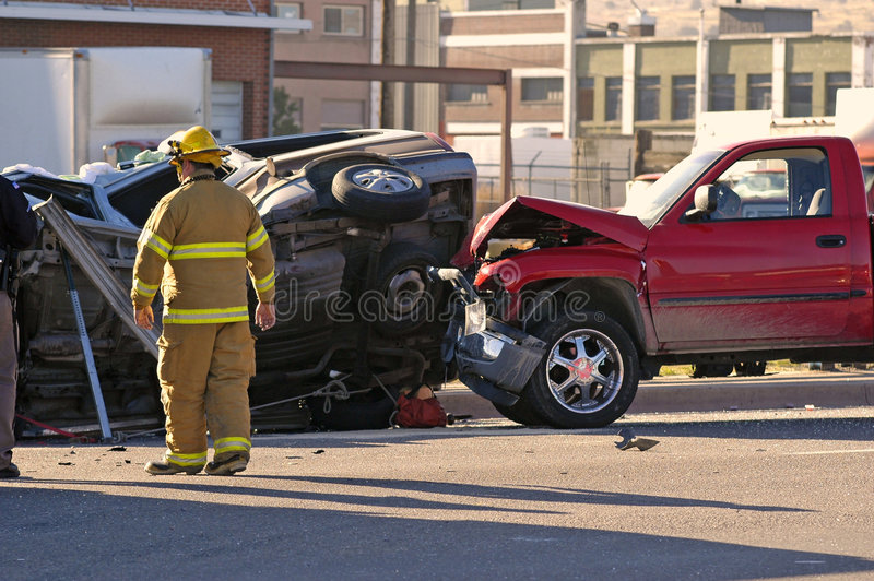 Car Accident. With a Fireman investigating the scene stock photography