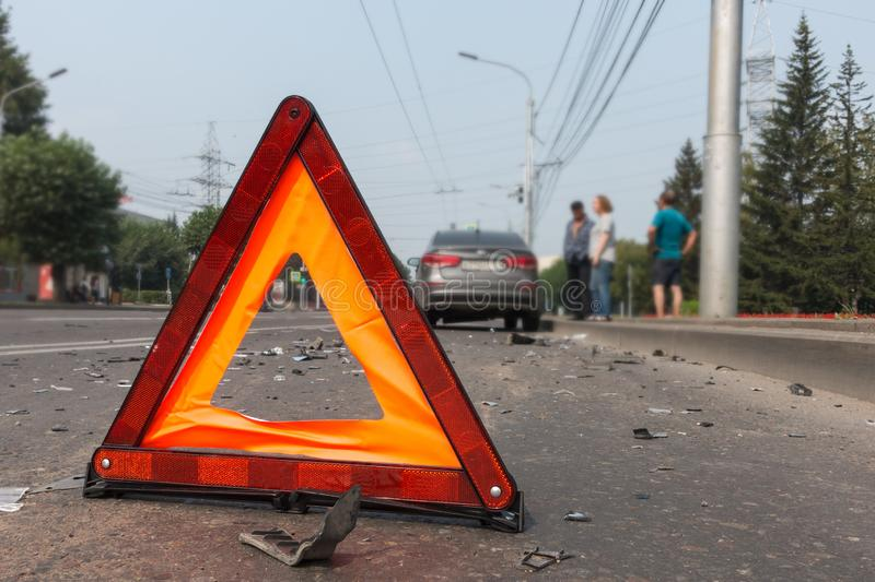 Car accident on a city street, road warning triangle sign.  royalty free stock image