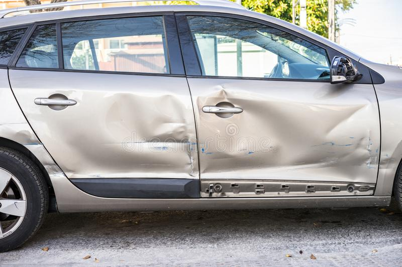 Car accident, damaged car doors at car side body. Close-up of dented silver car doors at car side body after car accident stock photography