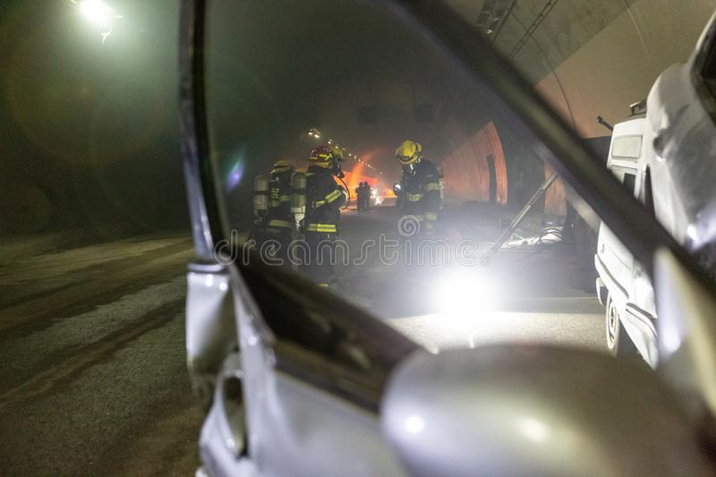 Car accident scene inside a tunnel, firefighters rescuing people from cars royalty free stock photo