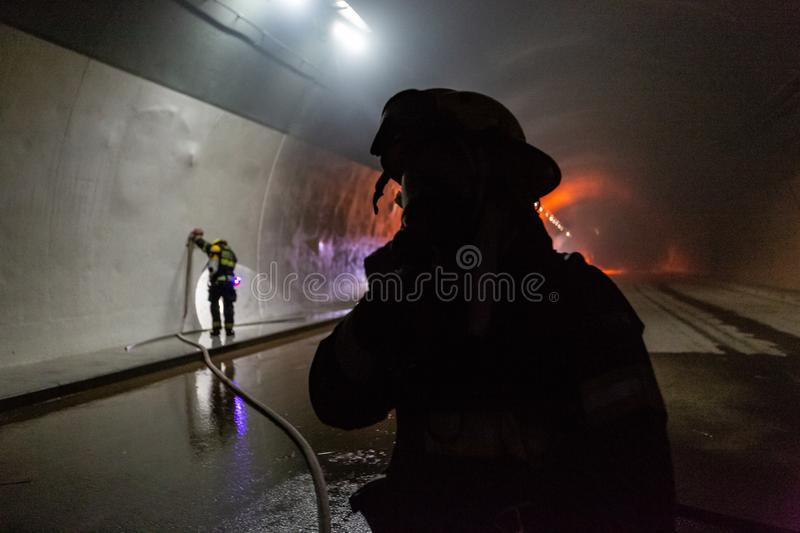 Car accident scene inside a tunnel, firefighters rescuing people from cars royalty free stock images