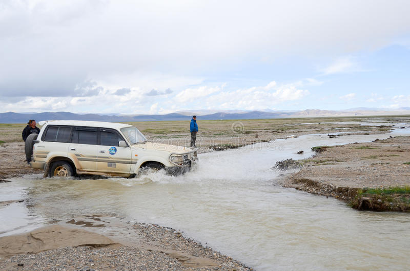 Car across the river in Tibet. Due to the high altitudes of Tibet, development lags behind, many places have no highway royalty free stock photo