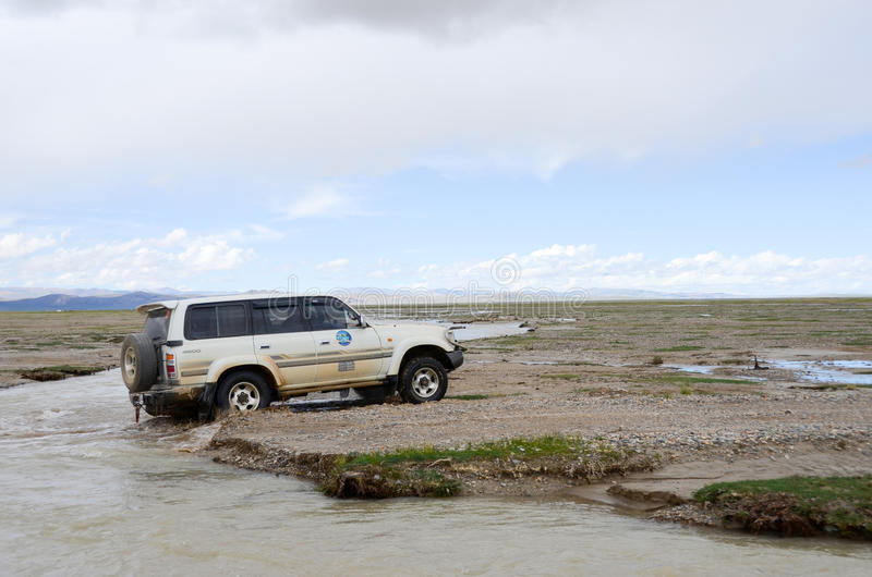 Car across the river in Tibet. Due to the high altitudes of Tibet, development lags behind, many places have no highway stock photo