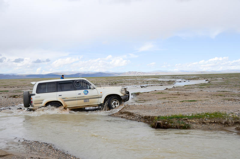 Car across the river in Tibet. Due to the high altitudes of Tibet, development lags behind, many places have no highway stock photos