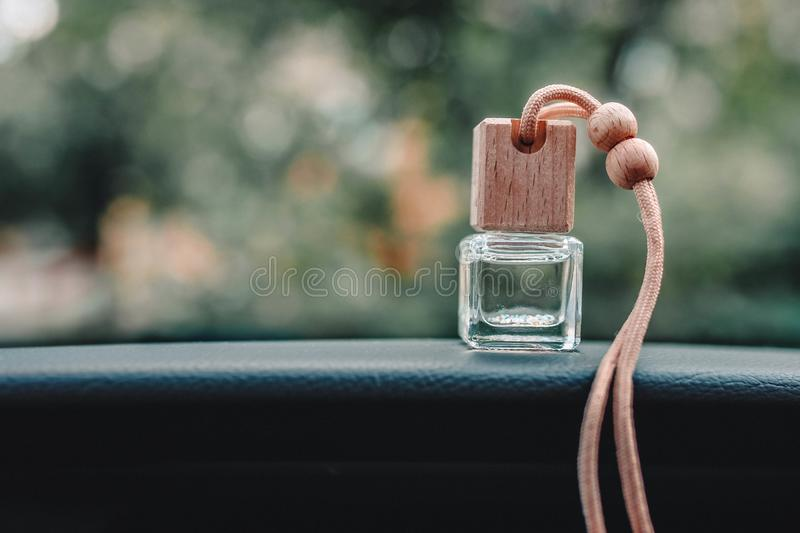 Car air freshener small bottle on the dashboard with beautiful blurred background outside the window royalty free stock photography