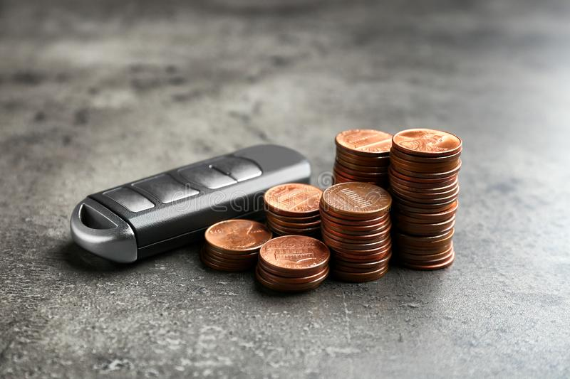 Car alarm key and coins. On grey background royalty free stock photos