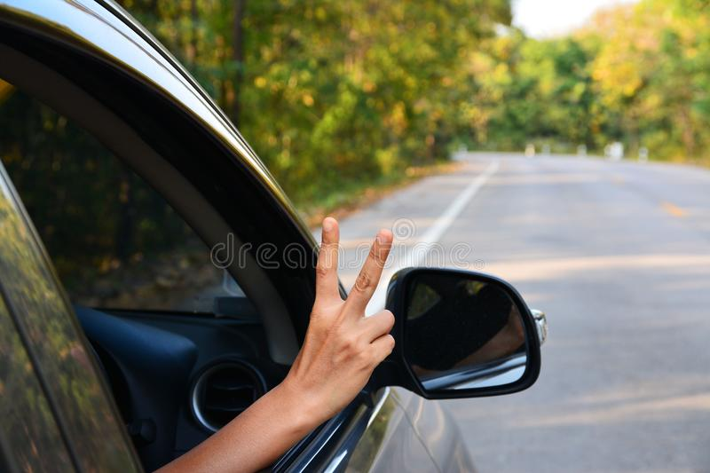 Car on asphalt road in nature with Hand. Out of the car royalty free stock image