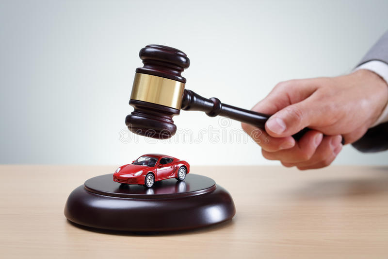 Car auction. Wooden gavel and red car concept for buying and selling at auction, speeding conviction, court appearance and prosecution royalty free stock photography