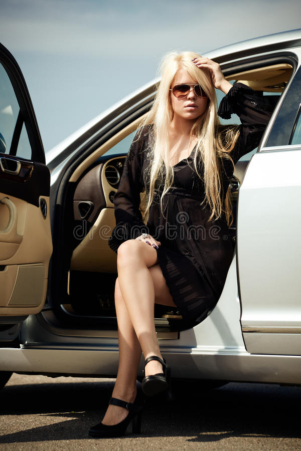 Car and babe. Young blond girl sitting in a luxury car stock image
