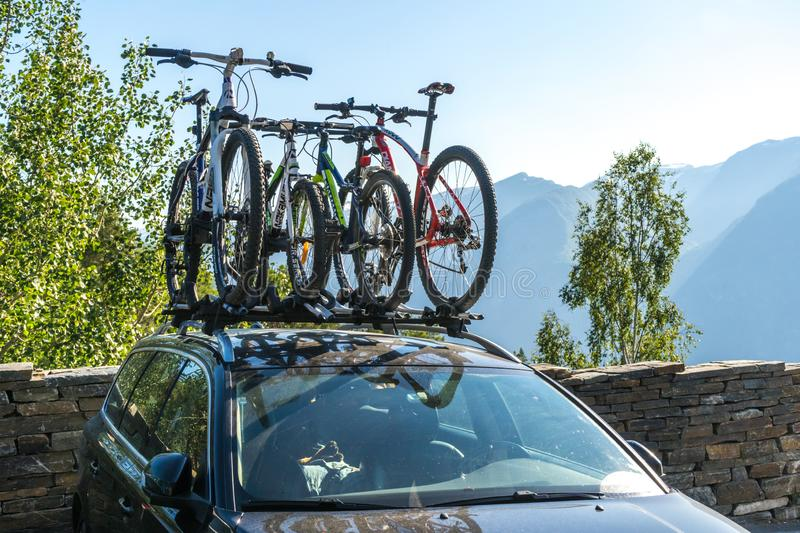 Car with 4 bicycles on the roof prepared for the family vacation outdoors. Two children and two adults bicycles. Concept of family stock photography