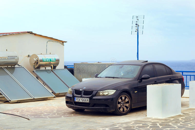 Car BMW parked on embankment. Bali, Crete, Greece. Bali, Greece - April 30, 2016: Contemporary black sports car BMW parked on embankment next to solar panels royalty free stock images
