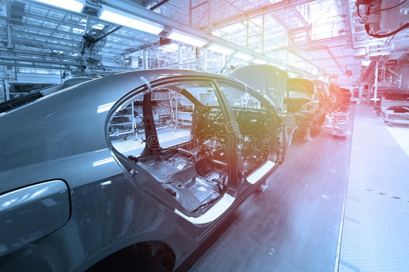 Car bodies are on Assembly line. Factory for production of cars in blue. Modern automotive industry. Blue tone. Empty car bodies are on production line stock image