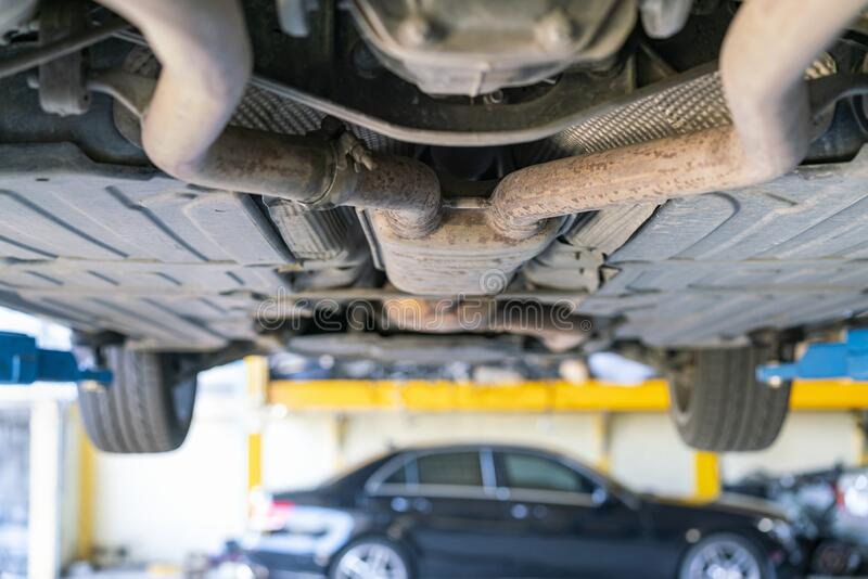 Car bottom view double or two exhaust suspension pipe system of saloon or sedan car at garage lift up for maintenance stock photography