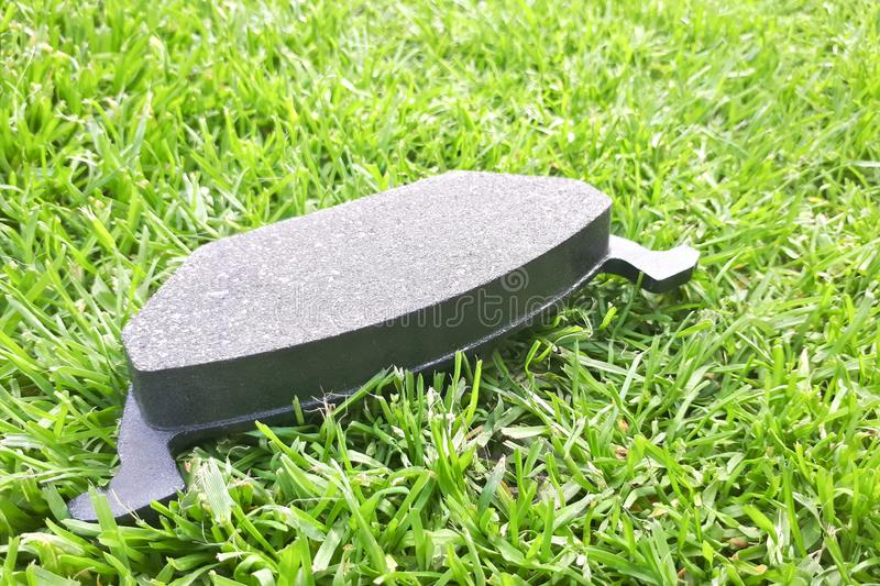 Car brake pad on green grass background. New car brake pad on green grass background royalty free stock photography