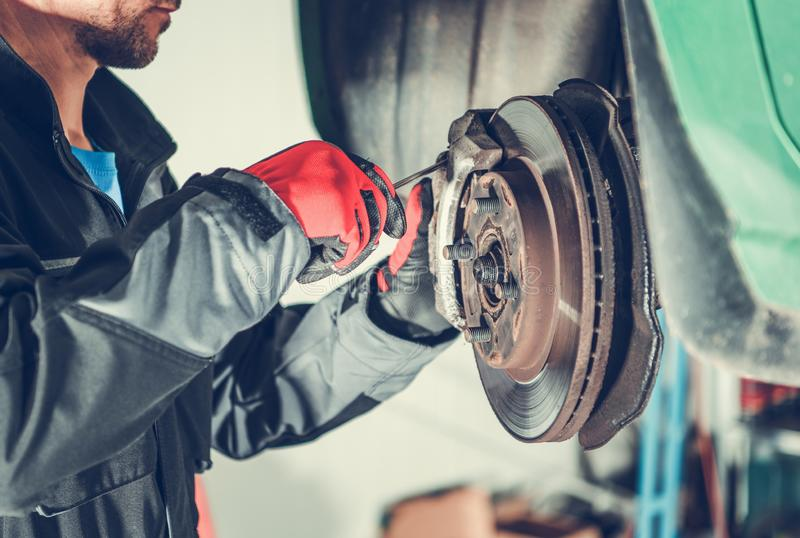 Car Brakes Replacing. Car Brakes Servicing by Caucasian Vehicle Mechanic in His 30s. Automotive Industry stock photography