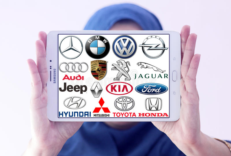 Car brands and logos. Arab muslim woman holding white tablet and most popular car logos and brands on display
