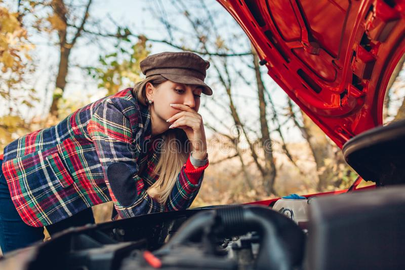 Car breakage. Confused woman opened hood of her auto that stopped on road and looking on engine gear. Driver has no idea what to do stock images